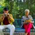 Two senior citizens sitting on a bench in a park